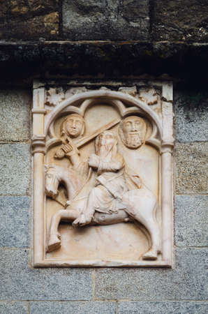 Gothic bas relief of a knight on the external wall of a medieval church
