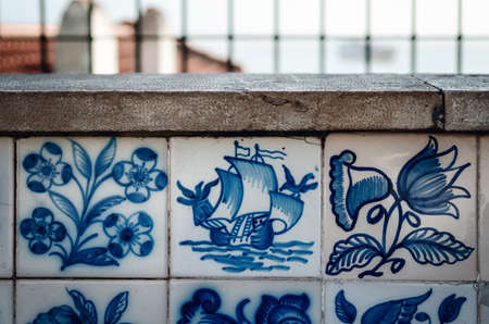 Porguguese caravel ship painted over traditional Azulejos in Lisbon, portugal, where is easy to find hand painted glazed blue and white tiles over the walls of the city Archivio Fotografico