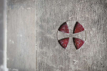 Ancient medieval templar cross engraved over the external stone wall of the cathedral of Lisbon, Portugal