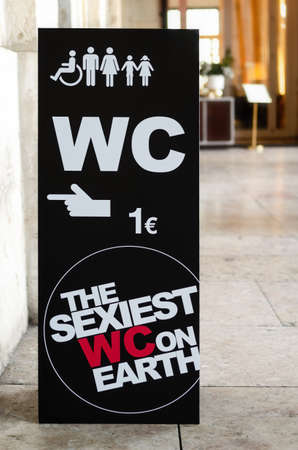 LISBON, PORTUGAL - FEBRUARY 3, 2019: funny black signboard in the streets of Lisbon, Portugal, pointing to a nearby public toilet with ironic message (the sexiest wc on earth) on february 3, 2019