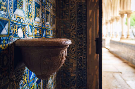 ancient stone holy water font in a chapel of a medieval portuguese monastery, decorated with traditional painted blue tiles Editorial