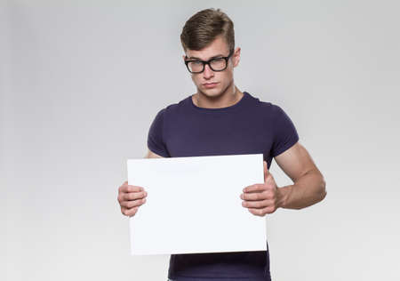Handsome young man holding a white board in a studio with grey background. Stock Photo