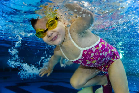 happy cute girl toddler swimming underwater photo