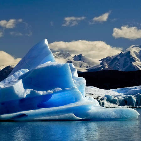blue iceberg resulting from melting glaciar is drifting away on Argentino lake, Patagonia, Argentina