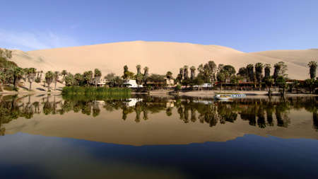 reflection of sand dunes in oasis lake