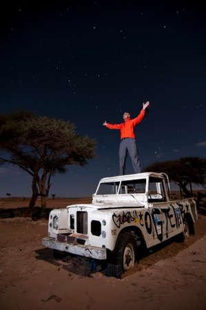 bonne aventure: homme debout avec les bras levés ouverts sur le toit brisé bloqués véhicule hors route, au milieu du désert, la nuit, l'exposition à long Éditoriale