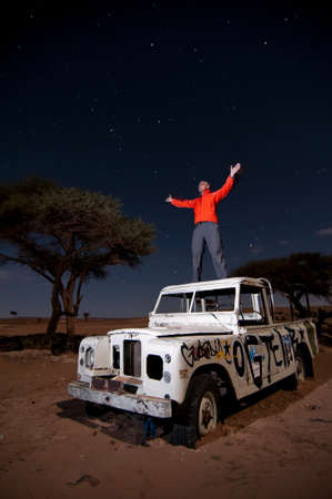 man standing with raised opened arms on broken stranded off-road vehicle roof,  middle of the desert, by night, long exposure