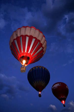 three hot air balloons flying by night
