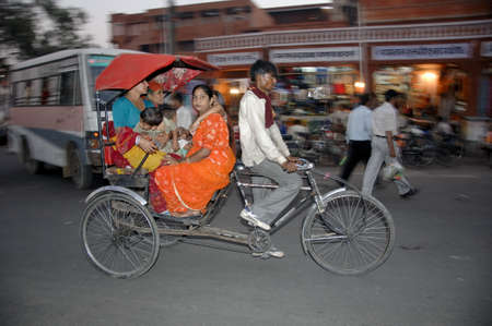 live work city: rickshaw driver taxis women and children in downtown jaipur, india