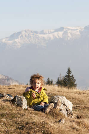 biscuts: happy curly haired toddler girl eating biscuts on meadow with snow capped mountains background Stock Photo