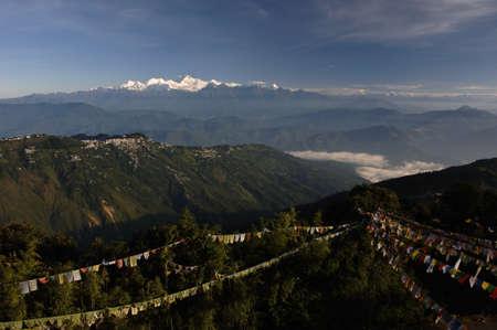 landscape with buddhist payer flags, town of darjeeling and himalaya khangchengdzonga mountain range
