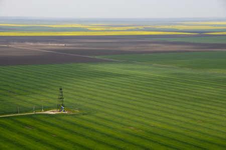 oilfield: aerial view of single oil well in green crops field