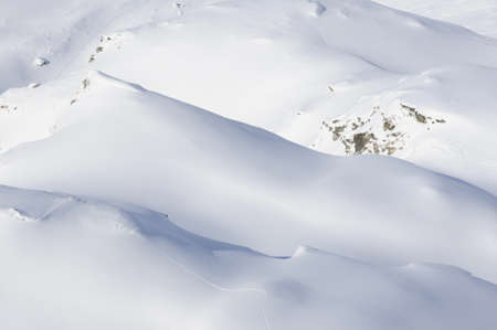 offpiste: aerial view of snow covered white mountains with single tracks