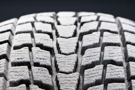 braking distance: studio close-up detail of winter tire tread full of snow Stock Photo