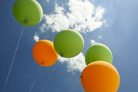 green and orange air balloons flying towards the sun with clouds and blue sky background