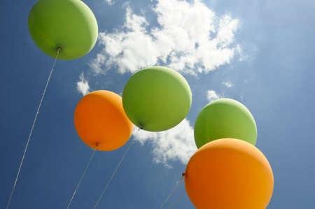 verde e arancione mongolfiere in volo verso il sole con nuvole e cielo blu Archivio Fotografico