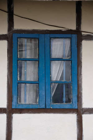 latticed: blue latticed window with curtain and brown framework  and white wall