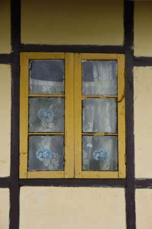 yellow latticed window with curtain and brown framework photo