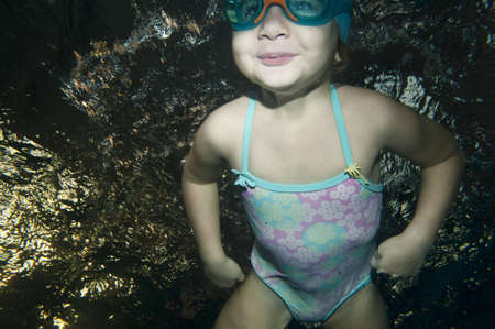 happy little toddler girl swimming underwater photo
