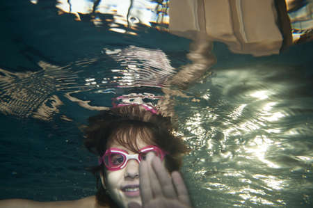 happy little girl playing underwater in swimming pool photo