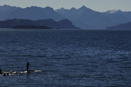 huapi: man quietly fishing on cliffs middle of the sea with mountain background