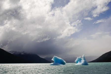 melting ice: two icebergs floating on the sea with mountains in the background