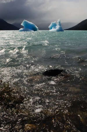 two icebergs floating on the sea with mountains in the background