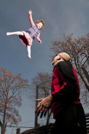 springboard: niño niña feliz saltando en trampolín asistido por el padre Foto de archivo
