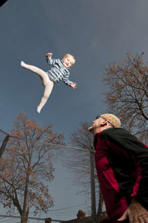 happy baby jumping up on trampoline assisted by father photo