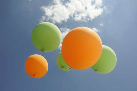 unchained: green and orange air balloons flying towards the sun with clouds and blue sky background