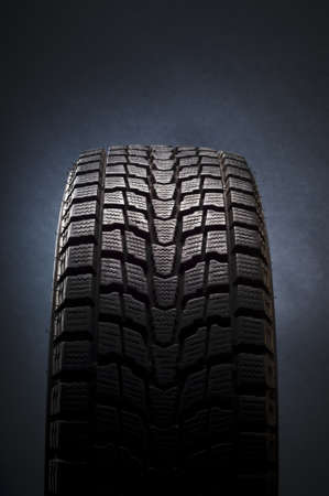 close-up detail of black winter tire in studio shot