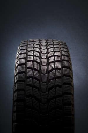tread: close-up detail of black winter tire in studio shot