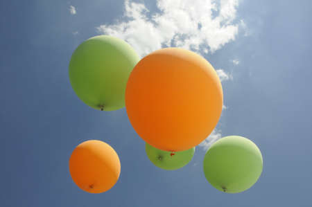 green and orange air balloons hover towards the sun with clouds and blue sky background