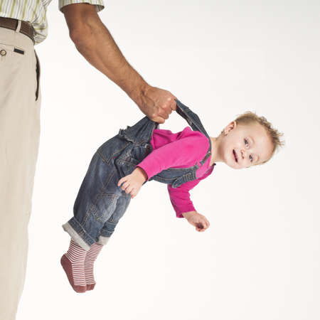concept of caring, father holding happy baby toddler girl suspended by suspenders Standard-Bild