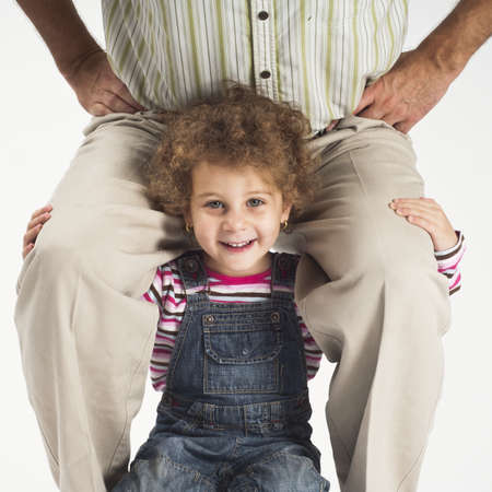 concept of overload,happy toddler girl holding father on shoulders