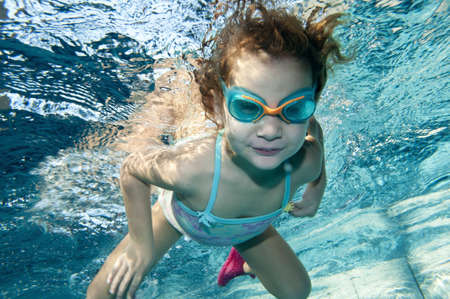 happy little toddler girl playing underwater in swimming pool photo