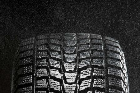 studio close up of wet winter tire tread in the rain