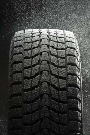 braking distance: one winter tire  in  snow flakes Stock Photo