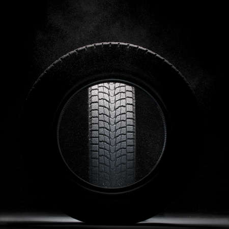 braking distance: black snowed winter tire seen through the hole of another winter tire