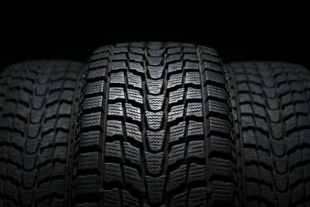 three black winter tires in studio shot Standard-Bild