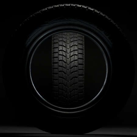 shorter: black winter tire seen through the circle of another winter tire
