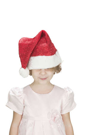 cute toodler girl wearing santa's hat on her eyes and smiling isolated on white Standard-Bild