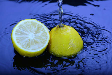 to watersplash: watersplash on yellow sliced lemon in blue water