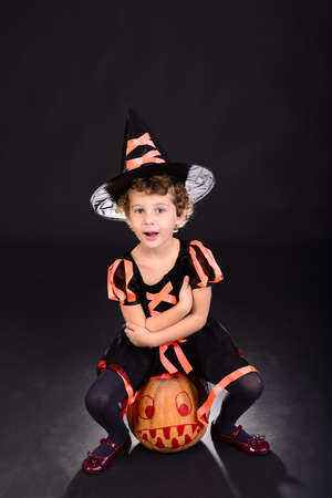funny 3 years old girl dressed in witch costume sitting on halloween pumpkin
