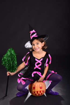 funny little girl dressed in witch costume sitting on halloween pumpkin