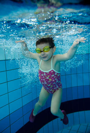 funny happy two years old toddler girl playing underwater in a pool with lots of air bubbles