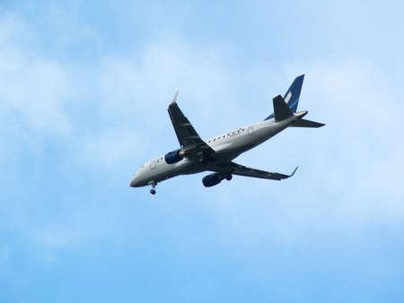 descending: White plane descending, on blue sky background Stock Photo