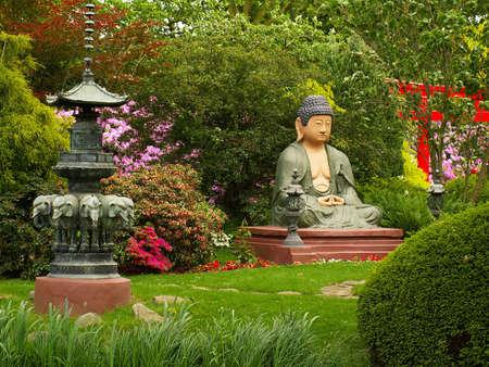 mindfulness: Boeddha in lotushouding bidden positie standbeeld in de Japanse tuin, horizontale foto
