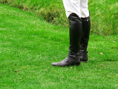 arena rodeo: Jockey wearing black leather riding boots