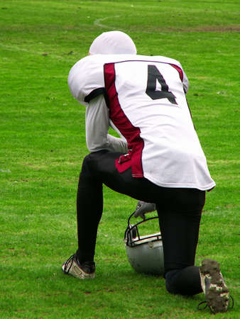 American football player kneeled on the side of the sport field Standard-Bild